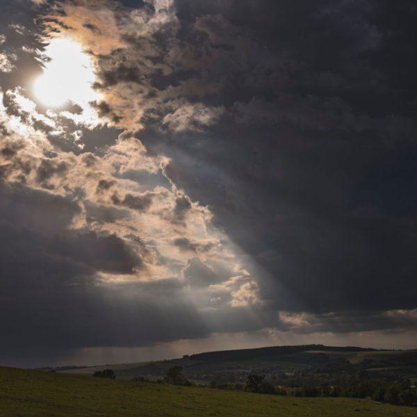 Hra slunečních paprsků mezi mraky